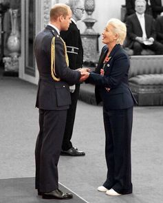 Emma Thompson receiving her Dame hood from Price William while wearing a Stella McCartney suit and Stella Stan Smiths.