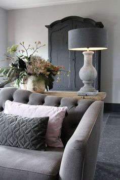 The velvet couch's texture is very smooth and bare but the throw pillows add balance with the texture.