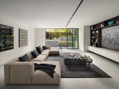 A living room with a glass wall opens to the terraced garden.