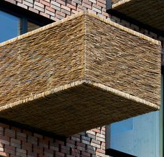 A protruding balcony made with a steel frame covered in woven wicker.