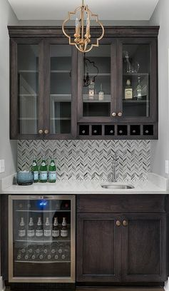 Exquisite brown wet bar boasts dark brown shaker cabinets accented with brass nobs and fitted in a nook beside a glass front beverage fridge located under a white quartz countertop.