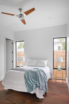 A simple guest bedroom idea, with side tables positioned in front of tall windows.