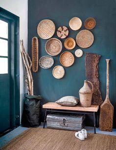 une entrée d'ambiance rustique aux murs peints en couleur canard foncé, déco ethnique chic en matériaux naturels