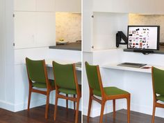 A modern kitchen with a computer monitor hidden in one of the cabinets to create a small home office.
