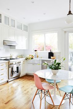 traditional white kitchen cabinets, brass pulls, cute little breakfast nook with pastel chairs