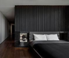 A textured black wood accent wall in a modern bedroom.