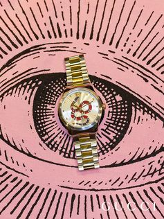 For Time To Parr, Gucci commissioned British photographer Martin Parr to capture the House's timepieces around the world. The Gucci Eye emblem watches over the piazza where travelers buy souvenirs, showing the new Gucci Eryx watch. This watch is designed with a traditional sensibility, juxtaposed with codes inspired by Gucci's new aesthetic. It displays house motifs, including the bee, the star and the heart.