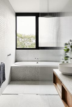Small grey square tiles cover the upper half of the bathroom walls, while large format terrazzo-style tiles are showcased on the lower portion of the walls and floor, where a linear shower drain can be found. #ModernBathroom #BathroomDesign #BuiltInBathtub #TexturedShowerScreen #GreyBathroom