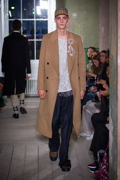 A double-breasted Chesterfield in tactile camel hair and wool is worn with a hand-embroidered tulle shirt, layered over a white jersey T-shirt. Complete with blue and white pinstriped trousers and a Vintage check baseball cap.