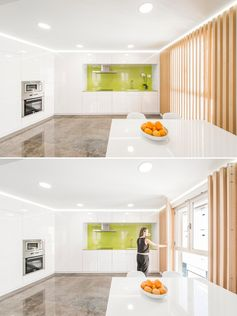 A wood slat wall covers the windows in this kitchen, but can be easily opened to let more natural light through.