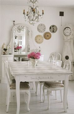 Une salle à manger blanche, de style Shabby chic, où la pendule de Mora a suspendu les heures en perdant ses aiguilles.