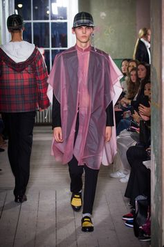 A pink soft-touch plastic poncho features over a fitted tailcoat in felted fine-wool. A white sweatshirt and riding trousers are added with black and yellow leather loafers and knitted cotton socks.