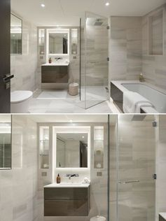 Neutral bathroom with glass enclosed shower and backlit mirror.