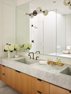 A master bathroom with a marble counter that has built-in sinks and sits on top of a wood vanity.