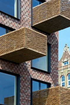 Woven wicker balconies protrude from a brick apartment building.