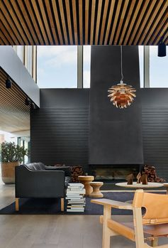Fireplace Ideas - In this modern living room, a large black steel fireplace commands attention, while a single pendant light anchors the rug and furniture in the open space. #ModernLivingRoom #LivingRoomIdeas #BlackLivingRoom #BlackFireplace