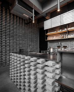 This modern coffee shop has a distinct grey brick pattern, that was installed at the counter bar and on the wall, adding a unique design element to the space. #GreyBricks #CoffeeShop #GreyBrick #InteriorDesign