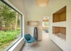This modern children's bedroom has built-in wood-lined bunk beds and a large picture window. #BunkBeds #BuiltInBunkBeds #ChildrensRoom #KidsRoom #Windows