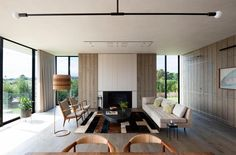 In this modern living room, wood clad walls surround the fireplace, while vertical windows on either side provide glimpses of the trees in the distance. #ModernLivingRoom #Fireplace #WoodWalls #InteriorDesign