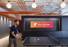 Studio BV have designed the Field Nation offices that were inspired by a circuit board and features orange conduit piping throughout, guiding people to the various areas of the office. #InteriorDesign #OfficeDesign #DesignAccent