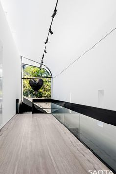 At the top of the stairs in this modern house is a window with views of the garden, and whose shape follows the line of the curved ceiling. #CurvedWindow #Windows #ModernHouse
