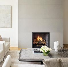 A smooth grey fireplace surround complements the interior, which has a neutral color palette.