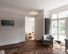 A large sliding door bridges the old and new areas of this home, while stained oak parquet flooring has been used throughout the ground floor. #ParquetFlooring #WoodFloors