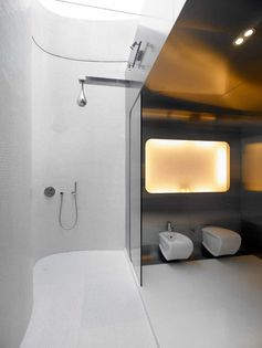 A modern bathroom with stainless steel walls, curved tiled walls, glass shower screens, and dual showers with a skylight.