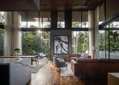 The social areas of this modern house are all open plan, with double height ceilings and large glass walls that open to let the breeze flow through. #ModernInteriorDesign #DoubleHeightCeiling #GlassWalls