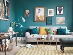un salon cozy qui associe le bleu paon aux tons ocre, mur en cadres qui reprennent les mêmes nuances