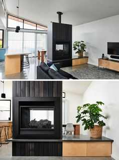 The main social areas of this modern house are open plan, with the living room enjoying one side of the double-sided fireplace, that features a black stained timber boards. #ModernFireplace #BlackStainedWood #FireplaceDesign #DoubleSidedFireplace