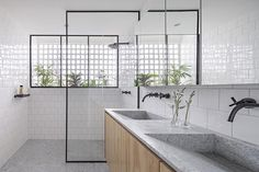 BLOCO Arquitetos has created a bright and modern bathroom featuring wood, grey granite, square white tiles, and black accents. #ModernBathroom #BathroomDesign #BrightBathroom #GreyAndWhiteBathroom