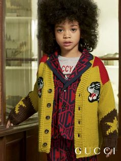 Yellow knit wool jacquard with star motifs on the sleeves and red and brown details with embroidered panther face patches on the front from the Gucci Fall Winter 2018 Children's Collection.