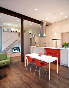 Wood floos, white table and island with orange chairs in an open living space showcase bright apartment storage ideas