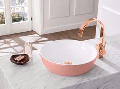 plan en marbre blanc, vasque rose pastel et robinet cuivrée