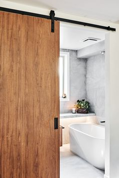 Door Ideas - A modern barn door with matte black hardware opens to reveal the bathroom. #ModernBarnDoor #DoorIdeas