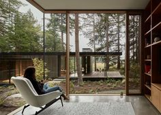 A structure from the main house is home to a library, and looks out to a courtyard of natural and native shrubs and ferns, and is surrounded by large Douglas Fir trees. #Library #Windows #GlassWalls