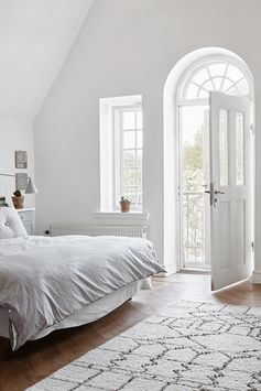 White bedroom with a balcony