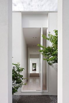 A modern house with a white exterior, that also has a pivoting white front door.