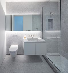 A modern bathroom with floor-to-ceiling grey penny tiles, a glass shower screen, a backlit mirror, and a floating vanity.