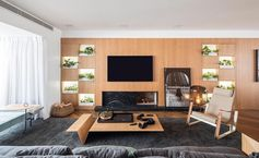 A wood living room wall with a fireplace and open shelves for small plants.