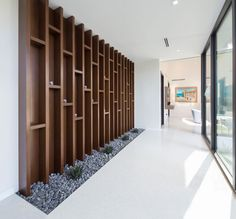 A large wood floor-to-ceiling open shelving unit in this hallway provides a place for the home owners to show off their decorative items, while the pebbles and plants at its base bring the outside in. #Shelving #Decor #InteriorDesign