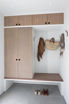 This modern mudroom has custom bamboo cabinetry with a built-in bench. To keep its design minimal, there are finger holes instead of hardware, and wood hooks on the wall. #Mudroom #ModernMudroom #EntrywayIdeas