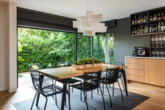 This modern and open plan dining room has sliding glass doors that open up an outdoor space. #ModernDiningRoom #DiningArea #SlidingGlassDoors #DiningRoomIdeas