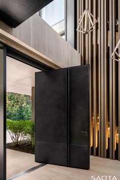 Welcoming visitors to this modern lake house is an oversized steel pivoting front door. #SteelFrontDoor #PivotingFrontDoor #OversizedFrontDoor