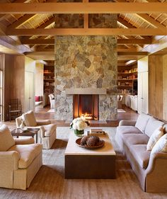 Fireplace Ideas - Exposed timber ceilings in this farmhouse modern interior, lend a sense of rustic refinement that is complemented by the stone fireplace that separates the den and living room. #StoneFireplace #FireplaceIdeas #LivingRoom