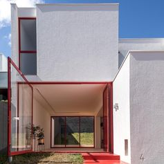 When the front door of this modern house is open, the large pivoting window can be moved by pushing the frame to open it up completely, exposing the interior of the home to the small grass patio. and front yard. #PivotingWindow #RedFrontDoor #WindowIdeas