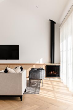 A modern living room with a custom oak and rattan cabinet and a black gas fireplace with exposed flue.