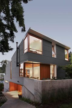A modern house with corrugated metal siding, concrete elements, and wood window frames.