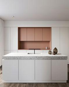 Cuisine moderne en blanc et rose avec îlot central et plan de travail en terrazzo